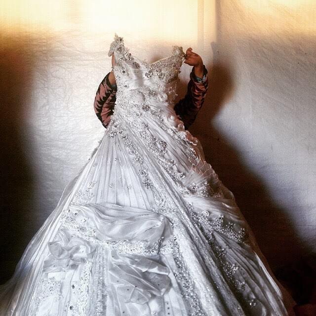 A wedding dress hangs in a refugee tent A motherhellip